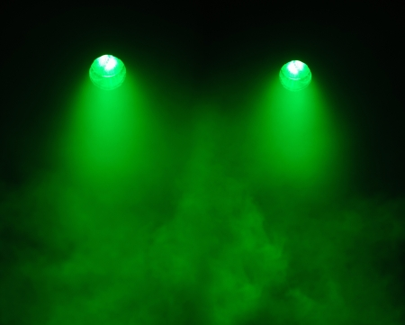 Two broad beamed green spotlights shining straight down through a very smoky atmosphere in darkness with the electrical elements visible in the lights photo