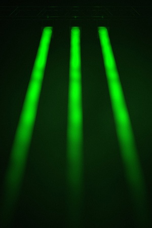 limelight: Three symmetrical narrow beamed green spotlights shining downwards through a smoky atmosphere with the outer two beams diverging at an angle into the corners of the frame