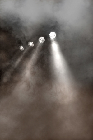 diverging: Line of white spotlights shining downwards through smoke and vapour filled air at a concert, disco or entertainment venue