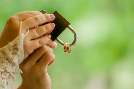 Gold wedding lock in couples hands. Bride holding a bright wedding bouquet with different