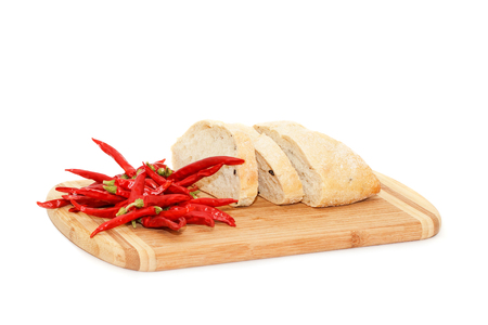 peper: Close view of hot peper and sliced bread lying on cutting board isolated over white background