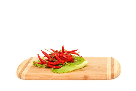 peper: Close view of red hot chili peper lying on green salad isolated over white background