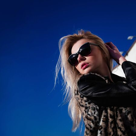 Girl in sunglasses outdoors in sunny weather posing. Urban portrait photo
