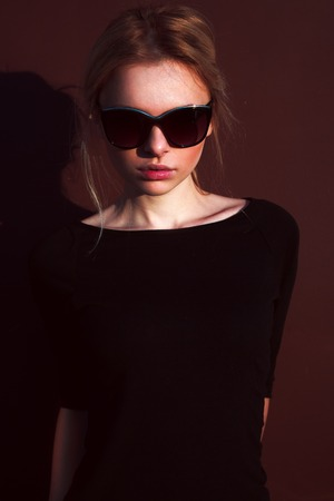 Girl in sunglasses outdoors in sunny weather posing. Urban portrait Stock Photo