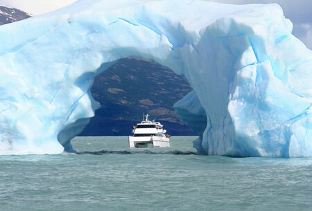 this ship seems that is navigating under the arc of an iceberg