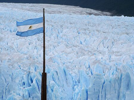 the argentinian flag over perito moreno glacier photo