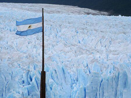 moreno glacier: the argentinian flag over perito moreno glacier Stock Photo