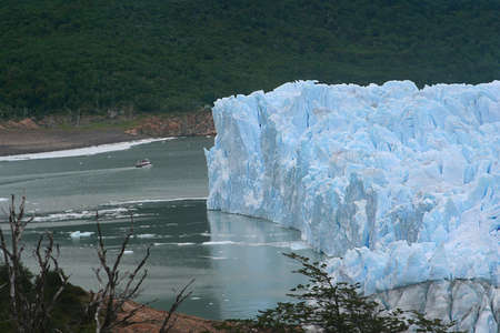 a ship is navigating close to the west side of the perito moreno glacier photo