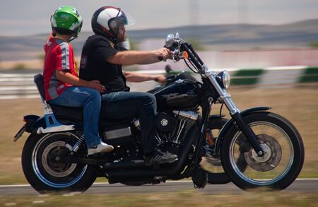 ALBACETE, SPAIN - JUN 5: rider driving a harley davidson with a child, in demonstration for FIA European Truck Racing Championship, on june 5, 2011, in Albacete, Spain.