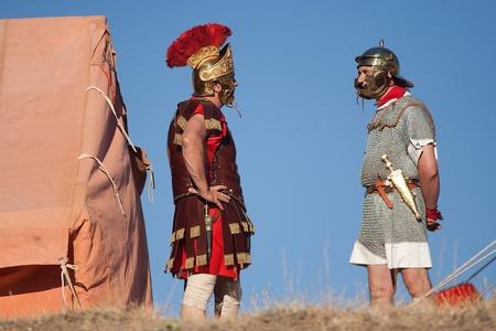 cascos romanos: VALERIA, ESPAÑA - 15 DE AGOSTO: los artistas no identificados vestidos como soldados romanos hablan en una exposición romana, en las antiguas ruinas de la ciudad romana Editorial