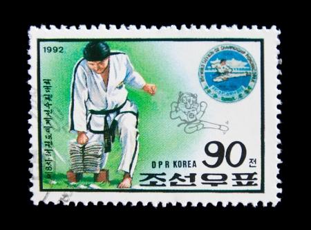 deportes olimpicos: RDP de Corea - CIRCA 1992: Un sello impreso por la RPD de Corea muestra a un hombre practicando el campeonato de taekwondo, la serie mundial de taekwondo, alrededor de 1992 Editorial