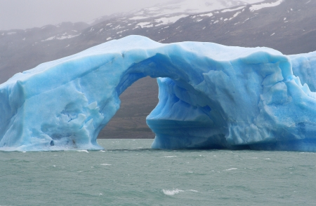 iceberg with an arch of ice floating in argentino lake, in the argentinian national park of glaciers