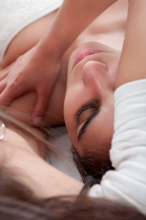 massage procedure in a shoulder of a young woman