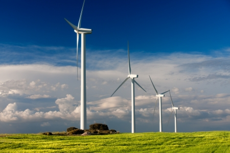 white wind turbine generating electricity on cloudy sky