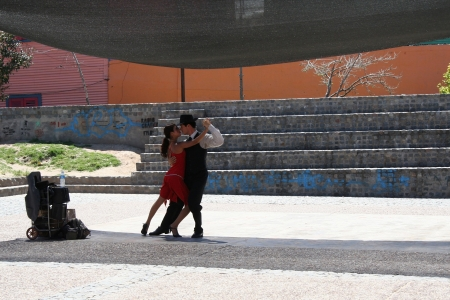 tangoing: BUENOS AIRES, ARGENTINA - NOVEMBER 13: A pair of tango dancers perform in the street in caminito, the famous area of Buenos Aires, on November 13, 2006, in Buenos Aires, Argentina Editorial