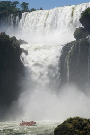 a boat is navigating between the iguazu falls near of the famous  garganta del diablo Standard-Bild