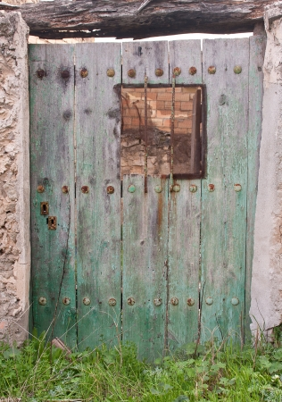 a view of a very old door made of wood with a small window, at the countryside photo