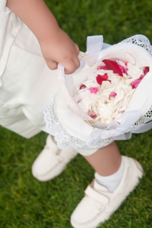 a child is holding a basket full of rose petals Stock Photo - 18339272