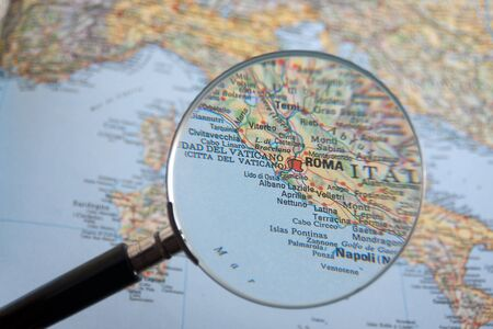 magnifying glass is used for examining an old map, and is focused in rome