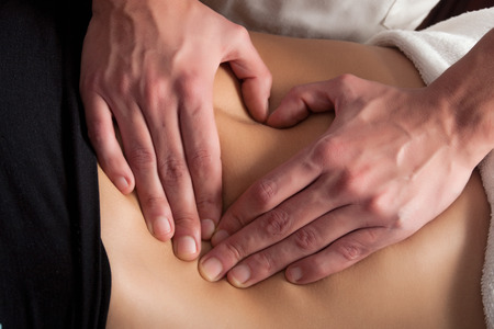 osteopathy: osteopathy procedure on the belly, forming a heart with the hands