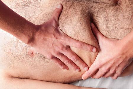 dolor de estomago: un hombre está dando un masaje en el vientre