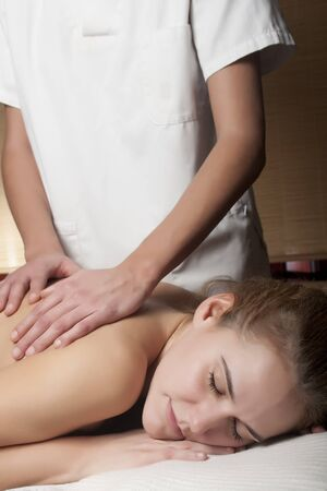 a young woman is taking a relaxing massage