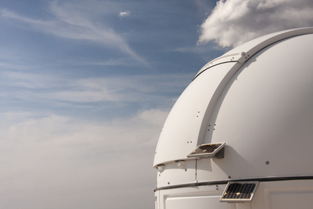 A dome, powered with solar panels, is containing scientific telescopes and is closed at daylight Stock Photo