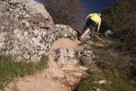 hikers climbing a hill, following a path in the countryside Standard-Bild
