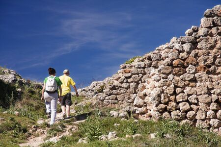 a couple of hikers walking among some ruins in the countryside