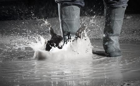 wearing waterproof boots in a rainy day Standard-Bild