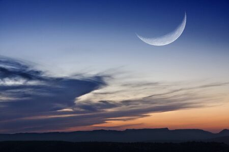 the moon in a crescent phase, over the horizon at sunset
