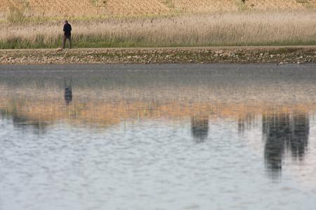 a man giving a walk by a lagoon