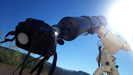 a telescope pointing at the sun while a camera is attached taking pictures Standard-Bild - 120024433