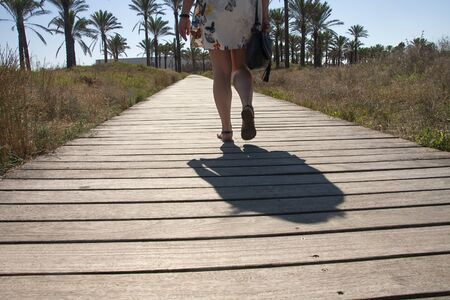 woman having a walk on a footpath in the coastline