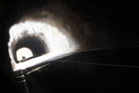 a car is getting into the darkness of a tunnel