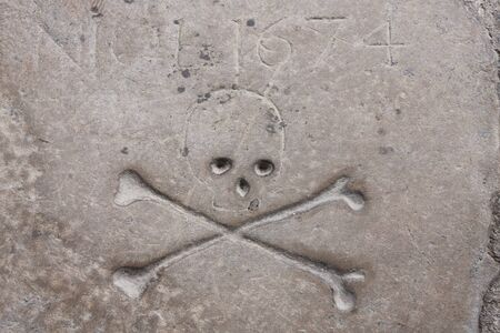 inscriptions and skull and bones of a very old tomb