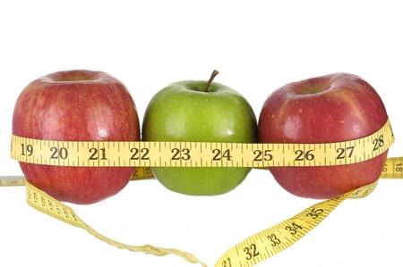 dieting: Rij van groene en rode appels met een meetlint eromheen. Stockfoto
