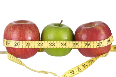 dieting: Row of green and red apples with a measuring tape around it.