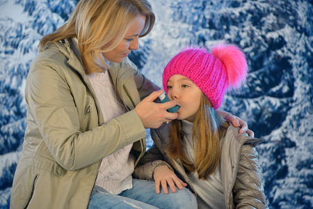 Girl using inhaler for asthma from his mothers hand in winter time