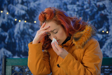 Outdoors portrait of  young woman sick colds,flu,fever outdoor Stock Photo
