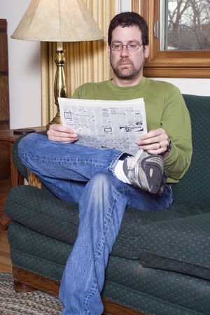 classifieds: Man at home on his couch, looking in the classifieds for a job