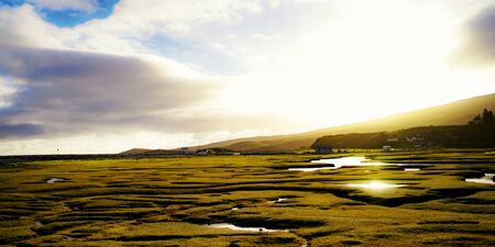 Achill Island, Mayo Ireland: Beautiful meadow with reflections on the water at sunset Stock Photo