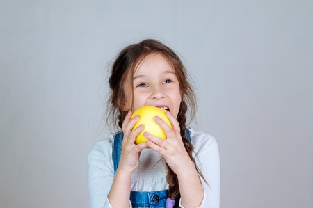 Emotional portrait little beautiful girl with pigtails in jeans overalls eating bites holding an apple. 6-7 years studio Banco de Imagens