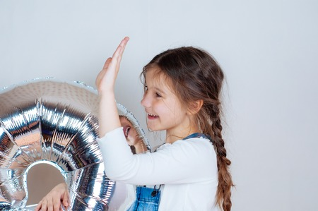 Happy beautiful little girl holding a silver gel balloon in the form of numbers. Birthday celebration.
