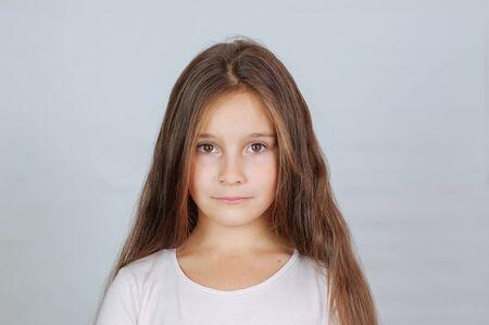 La piccola ragazza carina di 6-7 anni con i capelli molto lunghi esprime gioia emotiva e un sorriso su uno sfondo bianco Archivio Fotografico