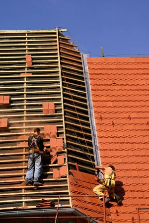 slate roof: Roof construction work. Workers with safety lines. Stock Photo