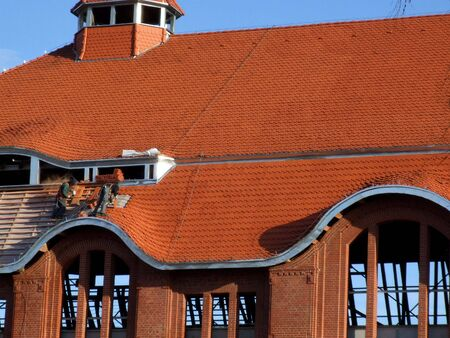 slate roof: Roofing works - dangerous construction job. Workers with safety lines.