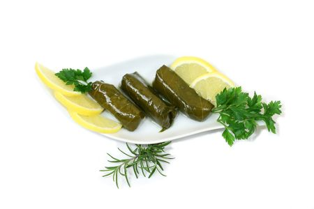 Greek or Turkish wraps - delicious stuffing wrapped in grape leafs. Common names: dolmade, dolmades, dolma, dolmadakia, dolmeh, yaprak, yapraci. May be stuffed with rice, zucchini, eggplant, tomato and pepper. Stock Photo