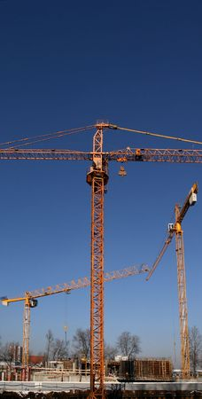dragline: Construction site with yellow cranes and blue sky Stock Photo