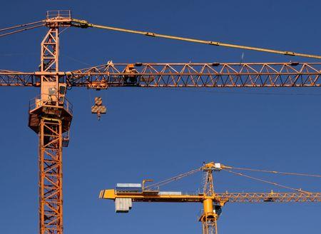 dragline: Industrial construction development. Yellow steel cranes against blue sky.